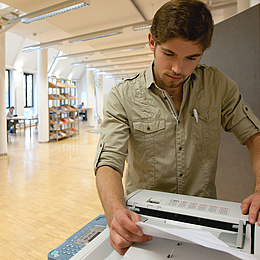 Young man next to a printer. Photo source: Lunghammer - TU Graz