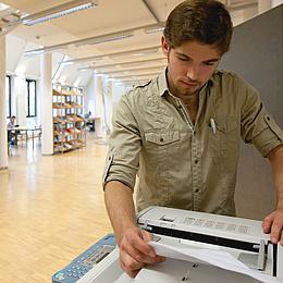 Ein junger Mann neben einem Standdrucker. Bildquelle: Lunghammer – TU Graz