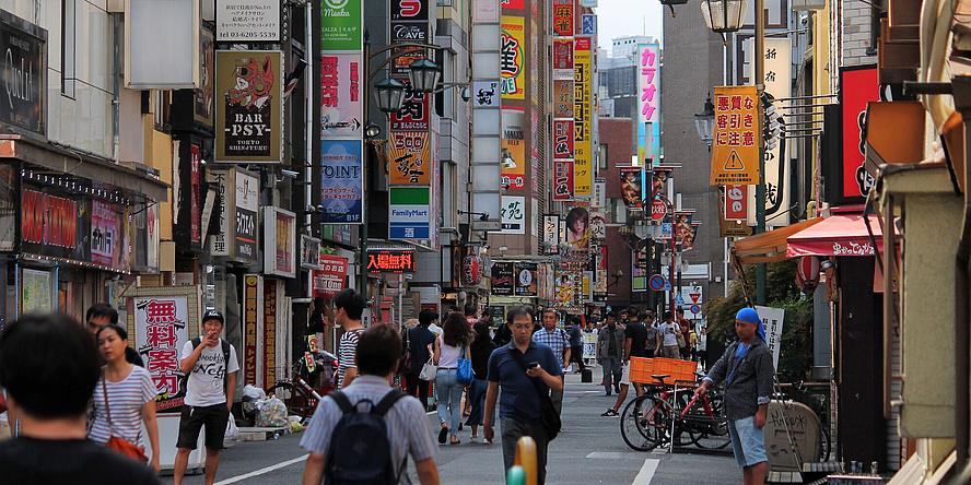 Eine belebte Straße. Viele Werbefahnen. Menschen spazieren herum.