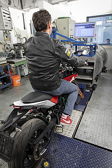 A man in a black leather jacket can be seen from behind; he is sitting on a motorcycle standing on a chassis dynamometer;