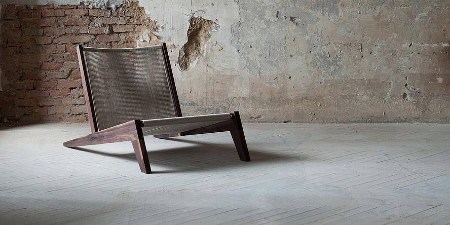 Loungesessel aus Nussholz und naturfarbenem Hanfseil vor teilweise grob verputzter Ziegelwand.