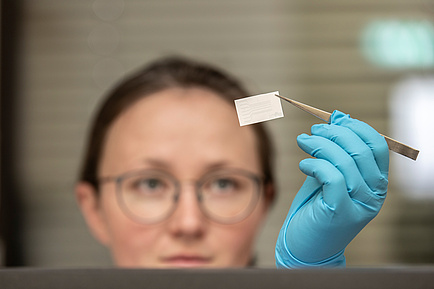 Researcher holds tattoo sensor with tweezers in the air