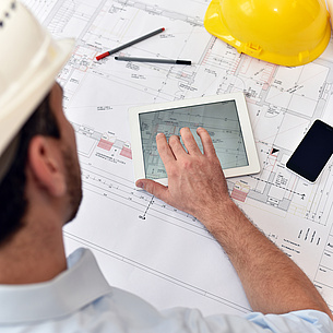 A man with a construction helmet, in front of him a table with construction plans, pens, tablet and mobile phone.
