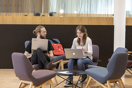 Eine junge Frau und ein junger Mann, beide mit Laptop, vertieft ins Gespräch.