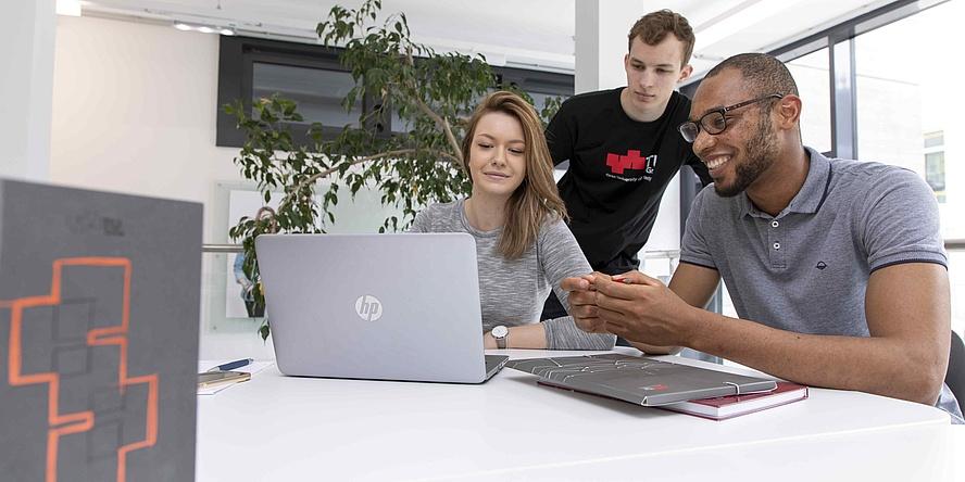 Zwei junge Männer und eine junge Frau mit Laptop und Arbeitsunterlagen an einem Tisch..