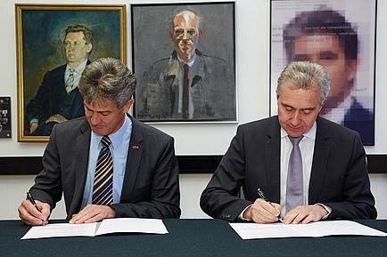 Zwei Herren im Anzug unterzeichnen an einem Tisch sitzend zwei Verträge.