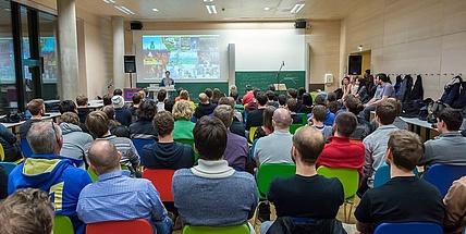 Viele Menschen sitzen in einem Hörsaal und hören einem Vortragendem zu.