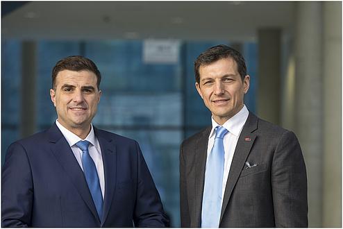 Zwei lächelnde Herren. Der Herr links trägt einen blauen Anzug mit hellblauer Krawatte. Der Herr rechts trägt einen grauen Anzug mit hellblauer Krawatte.