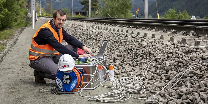 Ein Mann kniet neben dem Gleis und bedient ein Messgerät.