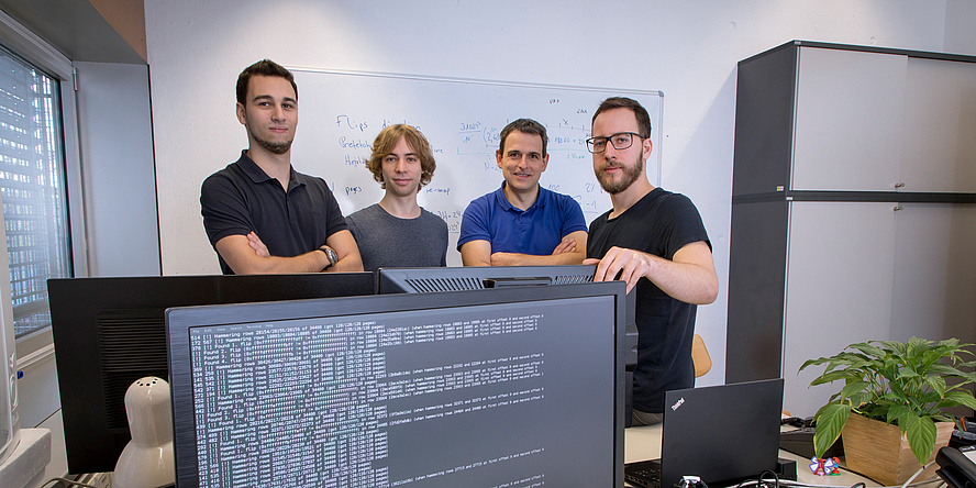 Four man are standing behind a black computer screen with white letters on it.