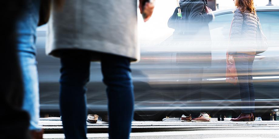 Wartende und gehende Personen vor und auf einem Zebrastreifen mit vorbeiziehenden Autos.