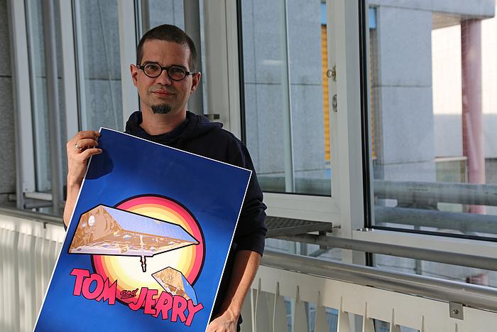 """Ein Mann mit dunklen Haaren und Brille steht in einem Gang. Er hält ein Poster in der Hand auf dem zwei Satelliten und der Schriftzug """"Tom und Jerry"""" zu sehen ist."""