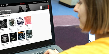 Frau nutzt Musikstreaming-Dienst last.fm am Desktop