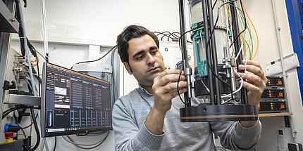 Mehrdad Imani Tilenoei arbeitet mit der Triaxialanlage.