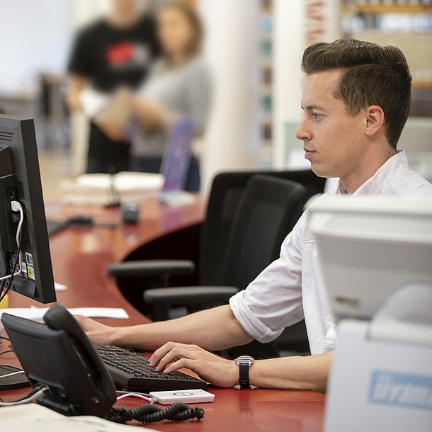 Ein Mann sitzt an einem Tisch vor einem Computer.