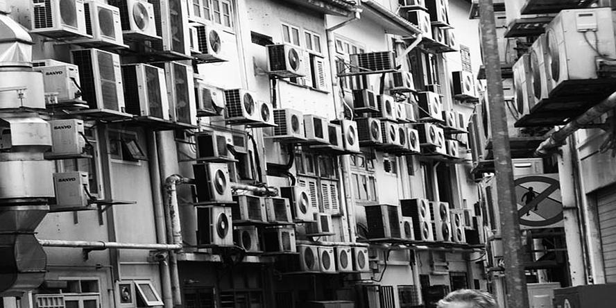 Schwarz-Weiß-Foto eines Hongkonger Wohnhauses mit Klimaanlagen an der Hausfassade.