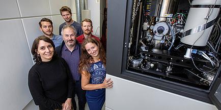 Eine Forschenden-Gruppe steht links neben dem Austrian Scanning Transmission Electron Microscope.