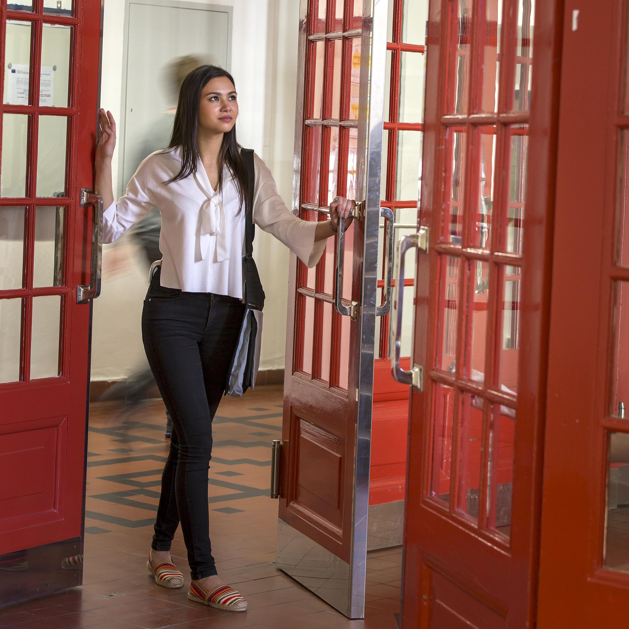Eine junge Frau geht entschlossen durch eine Tür.