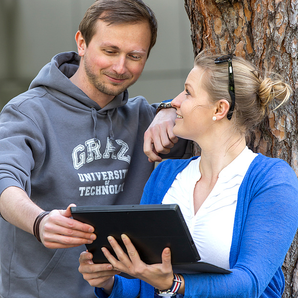 Young woman leaning against a tree and showing a young man something on her tablet. Photo Source: Lunghammer - TU Graz.