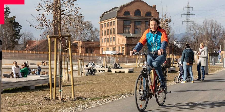 Mann am Fahrrad fährt durch belebten Park