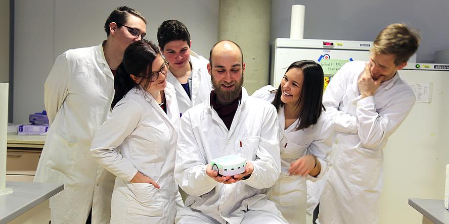 Sechs Mitglieder des aktuellen iGEM-Teams in weißen Kitteln in Laborräumlichkeiten.