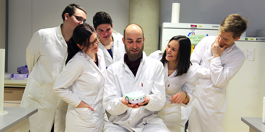 Six members of the current iGEM team in white coats in the laboratory.