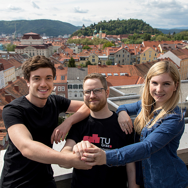 Two men and a woman holding hands. The man in the middle is wearing a T-Shirt of TU Graz. Photo source: Lunghammer - TU Graz