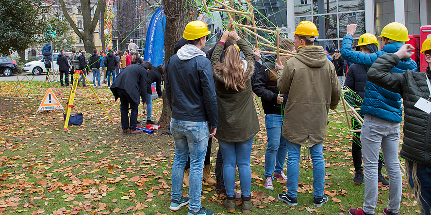 Schülerinnen und Schüler bauen auf einer belaubten Wiese hinter der alten Technik gemeinsam an einem Turm aus grünem Stabwerk.