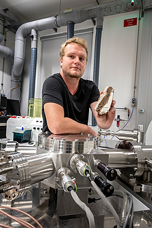 TU Graz researcher with rock sample in front of a mass spectrometer
