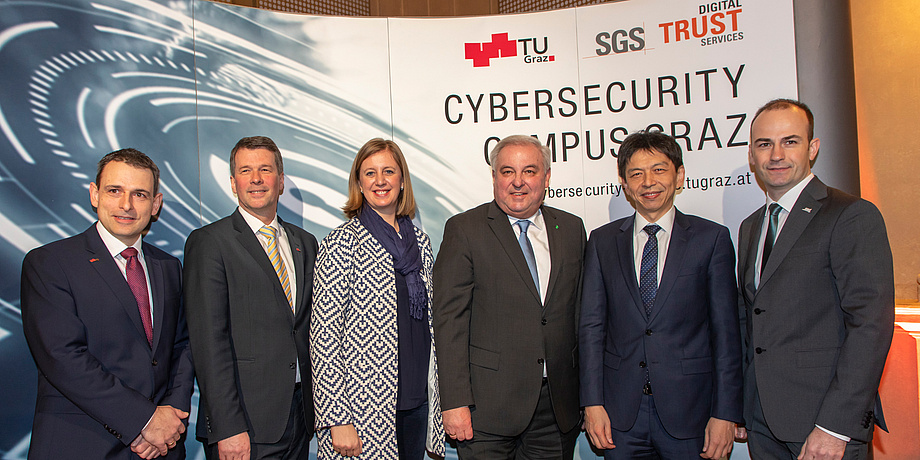 Five men and a woman are standing in front of an expo wall, on which the logos of TU Graz, SGS and the URL of the Cybersecurity Campus Graz can be read.