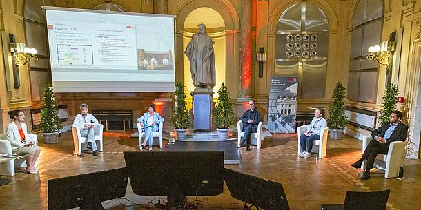 Sechs Personen sitzen in einem Halbkreis auf Stühlen in einem großen Raum. Vor ihnen stehen Monitore, dahinter steht eine Leinwand mit einer Präsentation.
