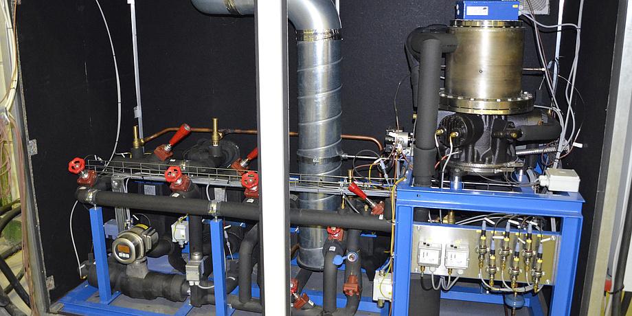 Eine Wärmepumpe: Viele schwarze Geräteteile und blaue Rohre.