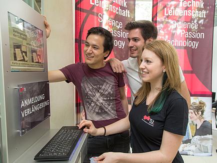 Drei Studierende bei einem Anmelde-Terminal an der TU Graz