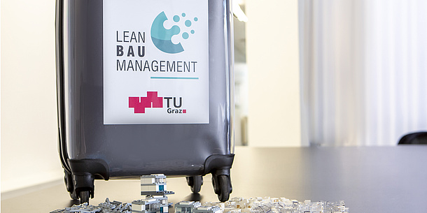On a suitcase on a table is written: Lean Baumanagement. TU Graz