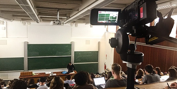 In the foreground is a video camera that records the events in the background: a professor in front of a full auditorium.