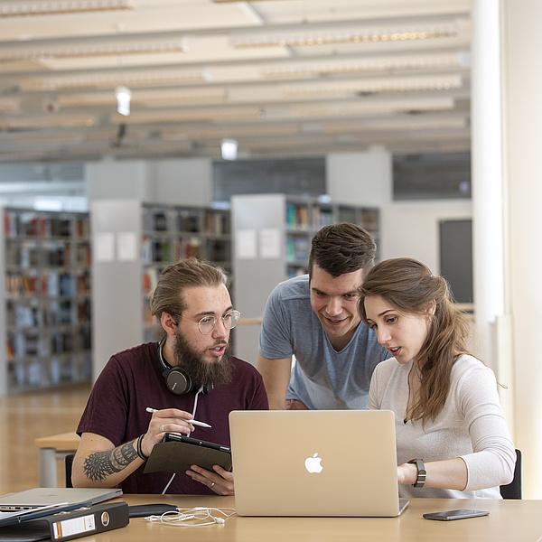 Drei junge Menschen sitzen in Bibliothek und schauen auf einen Laptop.