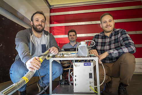 3 researchers with measuring device