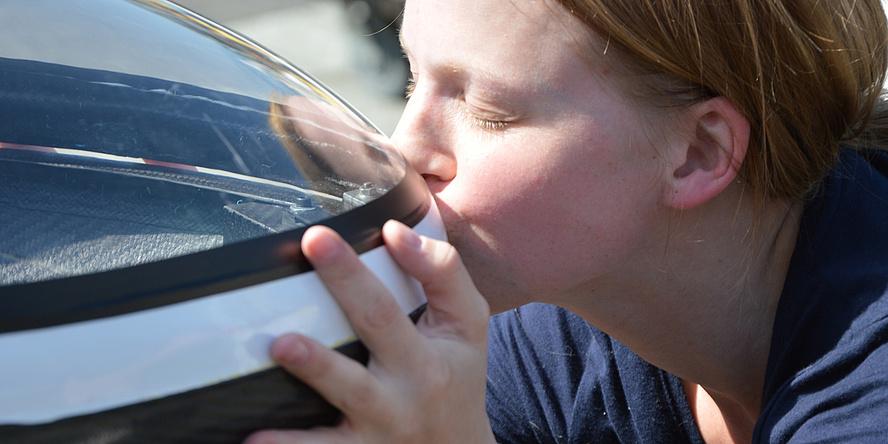 Eine Studentin aus dem TERA TU Graz-Team küsst die stromlinienförmige schwarz-weiße Spitze des siegreichen Fennek 2014.