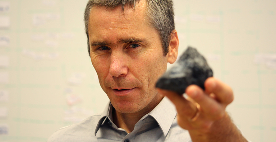 Roman Marte is holding a black rock.