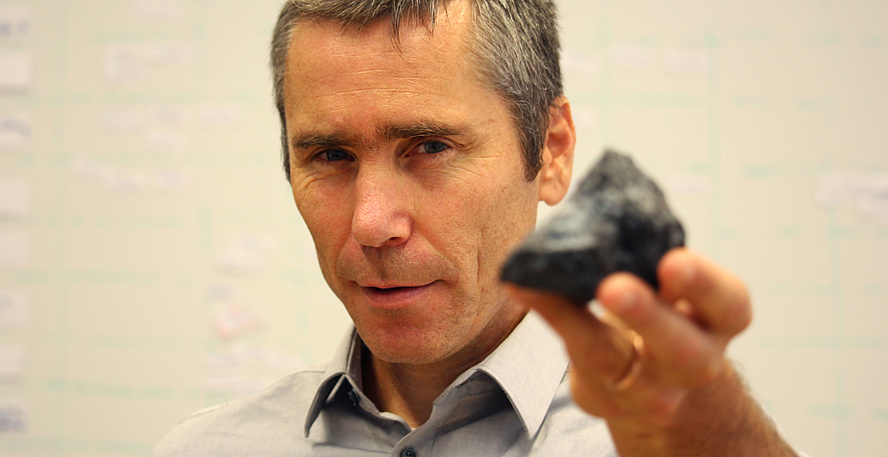 Roman Marte hält einen schwarzen, kantigen Stein in die Kamera.
