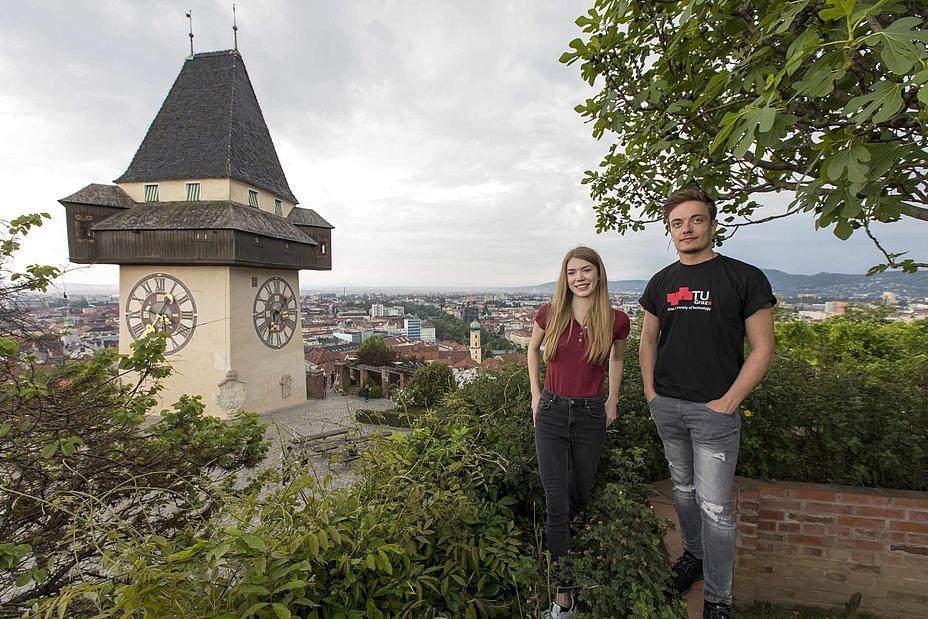 Ein junger Mann und eine junge Frau neben einem historischen Uhrturm.