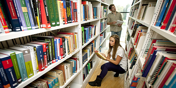 A man and a woman are standing between bookshelves.