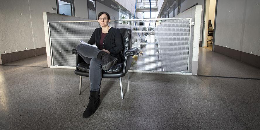 Eine junge Frau sitzt auf einem schwarzen Ledersessel vor einem Gang. Sie hat die Beine übereinandergeschlagen und schaut direkt in die Kamera. In der Hand hat sie mehrere Papierbögen.
