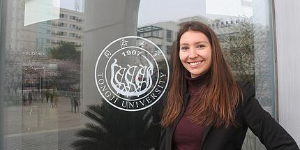 Clara Fischer vor ihrem Büro im Chinesich-Deutschen Haus der Tongji Universität, deren Logo sichtbar ist