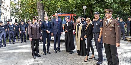 Sieben Männer und eine Frau vor dem Feuerwehrbus der Freiwilligen Feuerwehr der TU Graz.