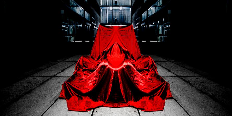 In einer Fabrikshalle steht im Zentrum ein Rennauto, dass von einem roten Samttuch verhüllt wird, sodass man nur die Silhouette sieht.