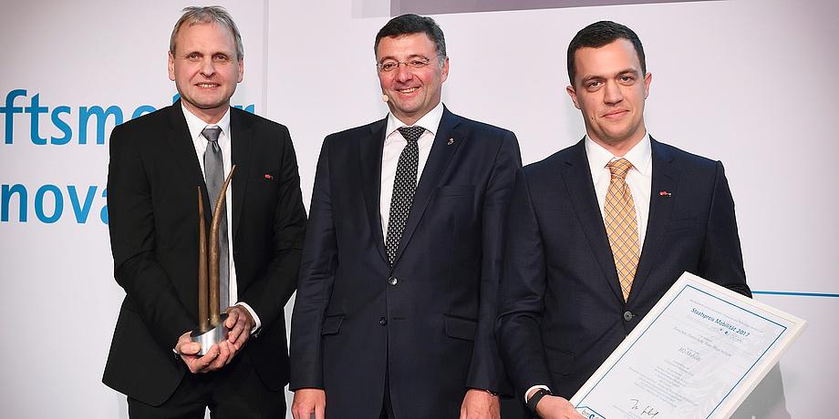 Drei Männer in schwarzen Anzügen lächeln in die Kamera. Einer davon hält eine weiße Urkunde in der Hand.