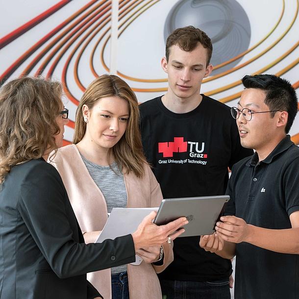 4 Personen schauen auf ein Tablet, eine trägt ein TU Graz T-Shirt