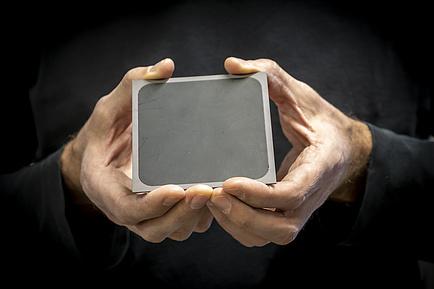 Zwei Hände halten ein graues Quadrat