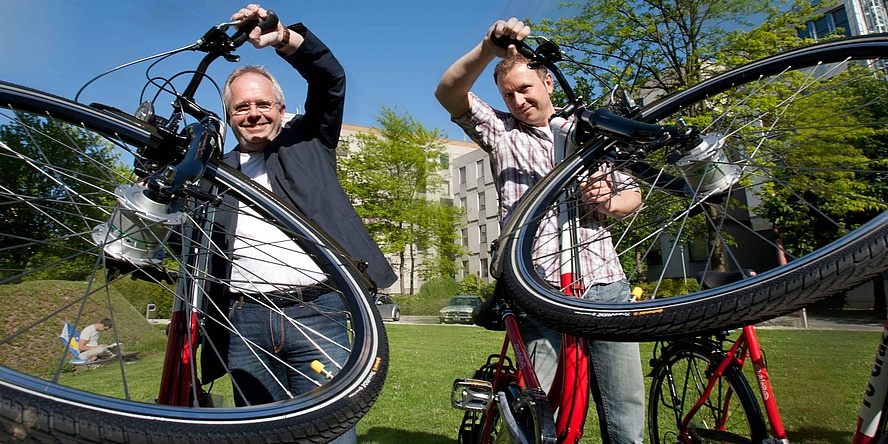 Two men on a city green hold their bicycles on their handlebars.